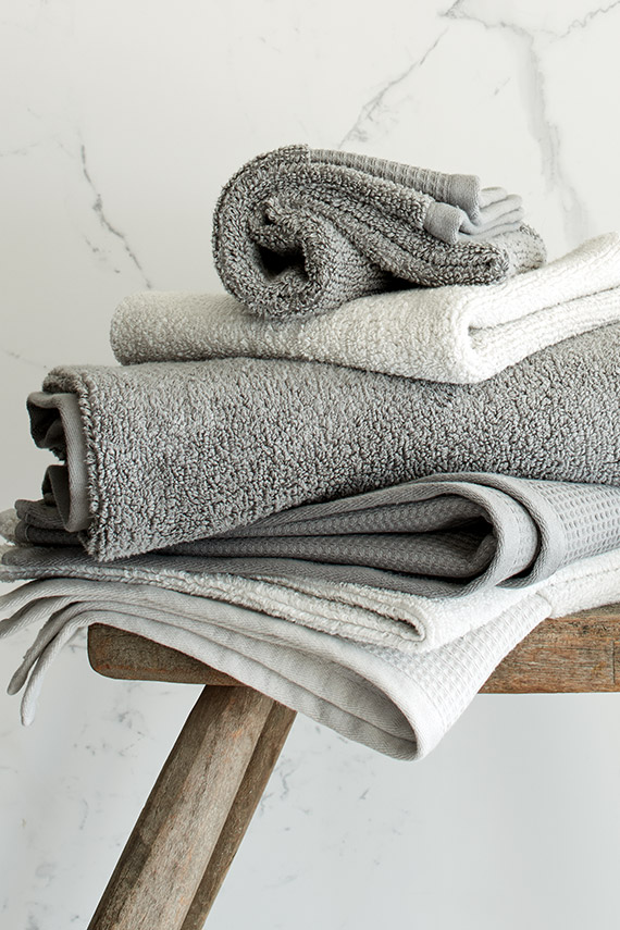 Stack of white and grey towels on stool