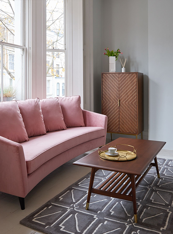 Pink sofa with dark wood furniture
